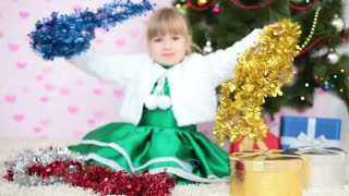 Laughing girl plays with Christmas decorations