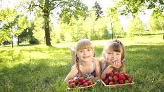 Laughing girls lying on the grass near strawberries