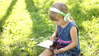 Laughing little girl in headphones is online with a Tablet PC