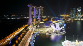 Lazar lights at night over the illuminated Helix Bridge and Marina Bay Sands Singapore. Marina Bay, Singapore, Asia, Time lapse