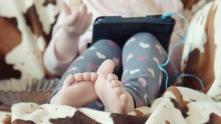 Legs, feet of the little girl sitting in a chair and watching video on the digital tablet
