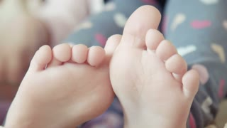 Legs of foot and fingers of the little girl sitting on the chair at home