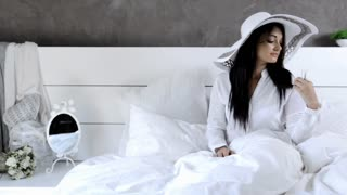 lifestyle beautiful brunette woman in white luxury bedroom