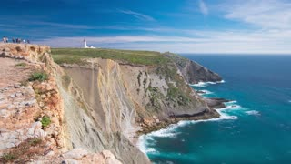 lighthouse of Cape Espichel with moving clouds near Atlantic ocean, view from the temple, Portugal timelapse, wide angle lens