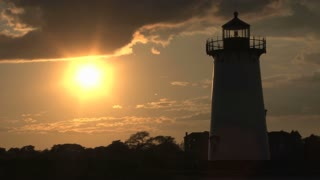 Lighthouse Silhouetted by Bright Sunset