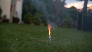 Lighting a firework in a suburbian backyard. Home firework during new year eve's celebration