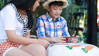 Little asian boy with mobile phone and teenage girl talk together