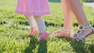 Little baby learns to walk. Slow Motion 240 fps. Mother is teaching her child to do the first steps on a green grass in summer. Close up on feet. Happy parenthood and childhood concept.