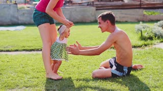 Little baby learns to walk. Slow Motion 240 fps. Young Parents are teaching their child to do the first steps on a green grass in summer. Toddler is learning to walk outdoors on a green lawn.