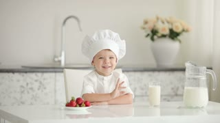 Little boy chef sitting at table and smiling