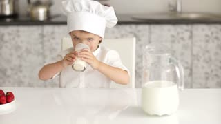 Little boy drinking milk with great pleasure