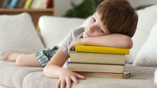 Little boy lying on sofa with stack of books