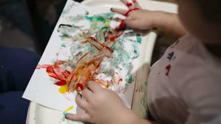 Little boy painting with colorful finger-paints. Activity for children.