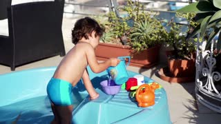 Little boy playing with bucket in paddling pool, slow motion shot at 240fps