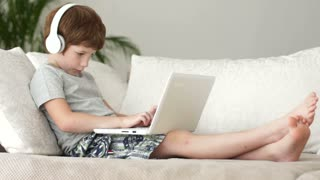 Little boy relaxing on sofa and using laptop
