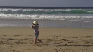 Little boy running on the beach, slow motion shot at 240fps
