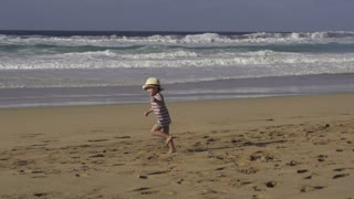 Little boy running on the beach, slow motion shot at 60fps