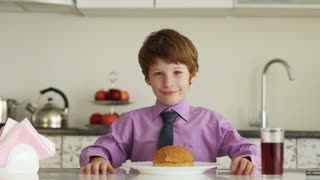 Little boy sitting at kitchen table and eating burger