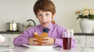 Little boy sitting at table eating burger and drinking juice