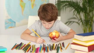 Little boy sitting at table holding apple and drawing with colored pencils