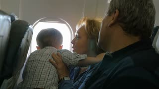 Little boy sitting on grandmothers lap and looking out plane window, grandfather trying to entertain him with paper plane. Family travel by air