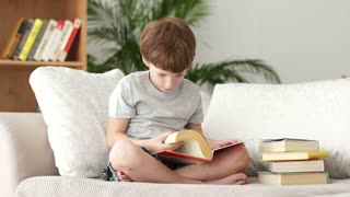 Little boy sitting on sofa and turning pages of book