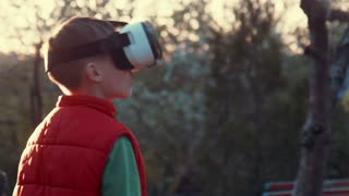 Little boy use virtual reality headset helmet, he very impressed