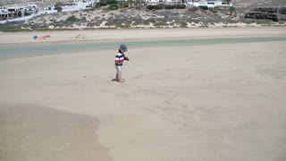 Little boy walking along the beach