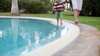 Little boy walking with his father beside swimming pool, steadicam