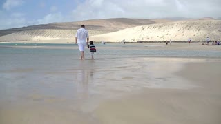 Little boy with father walking along the beach