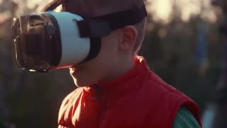 Little boy with surprise and pleasure uses virtual reality helmet and moves around itself outdoor