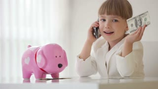 Little  businesslady talking on the phone and holding money in hand