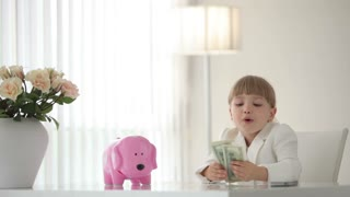 Little  businesswoman counting money and hugging piggy bank