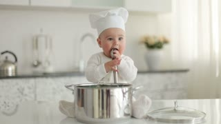 Little chef sitting in front of pan with spoon and eating something