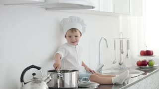 Little chef sitting with ladle and pan