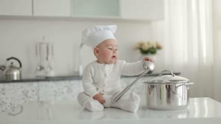 Little chef with a ladle knocking over a pan and laughs
