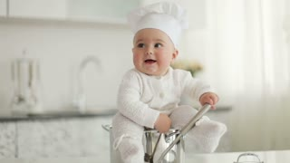 Little cook sitting in pot with ladle in hand