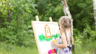 Little girl drawing a dream home in the park