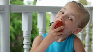 Little girl eating a big red tomato and smiling at camera. Child showing Ok. Thumbs up. Close-up