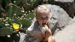 Little girl eating ice cream near the cactus in the desert