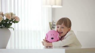 Little girl hugging a piggy bank with money