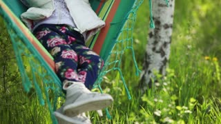 Little girl is resting in a hammock in the park near the house