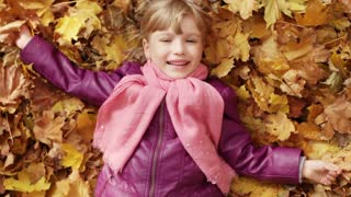 Little girl lying in yellow leaves. Autumn leaf fall. The child lying on the ground looking at the camera and laughing