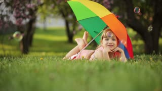 Little girl lying on grass with umbrella
