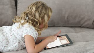 Little girl lying on the couch and playing on the tablet pc