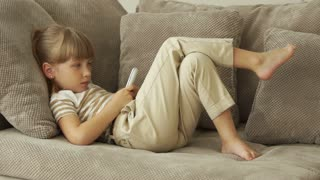Little girl lying on the sofa and writing sms