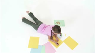 Little Girl on Stomach Drawing Picture with Crayons Camera Crane Move