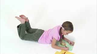 Little Girl on Stomach Drawing with Crayons