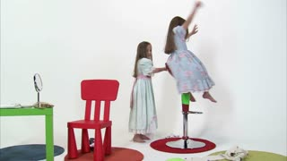 Little Girl Playing on Tall Chair with Her Twin