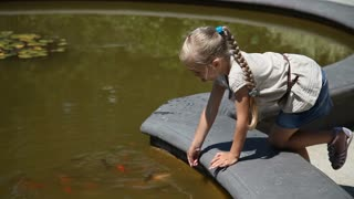 Little girl playing with a fish which living in a pond